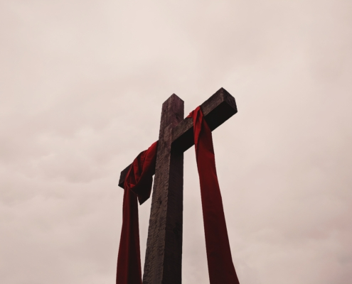 low angle view of cross with red garment